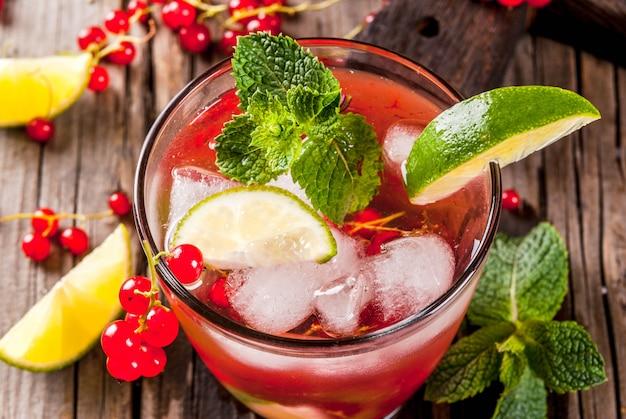 夏の飲み物、食事の健康的なカクテルのアイデア。ライム、ミント、レッドカラントのモヒート。