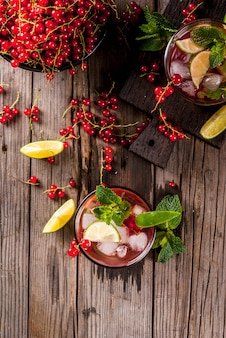夏の飲み物、食事の健康的なカクテルのアイデア。ライム、ミント、レッドカラントのモヒート。上面図