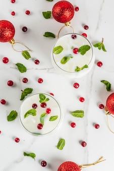 秋と冬の飲み物、ホワイトクリスマスモヒートカクテル、クランベリーとミント、白いテーブル、コピースペーストップビュー