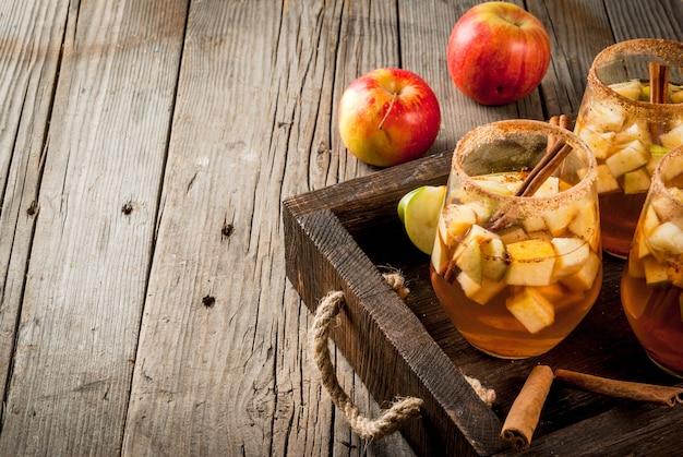 秋と冬の飲み物。温かいアップルサングリア、フルーツ、シナモンの入ったアップルサイダー