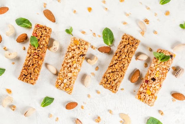 Здоровая закуска. фитнес. диетическое питание четыре зерновых батончика мюсли с орехами и фруктовыми ягодами