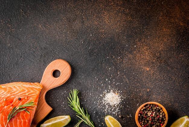 新鮮な刺身サーモン、ステーキの切り身、スパイス、ライム、ローズマリー、塩、暗いさびたシーントップビュー