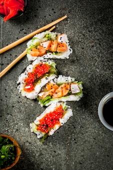 トレンドハイブリッド食品。日本アジア料理。ミニ寿司タコス、サーモンのサンドイッチ、林わかめ