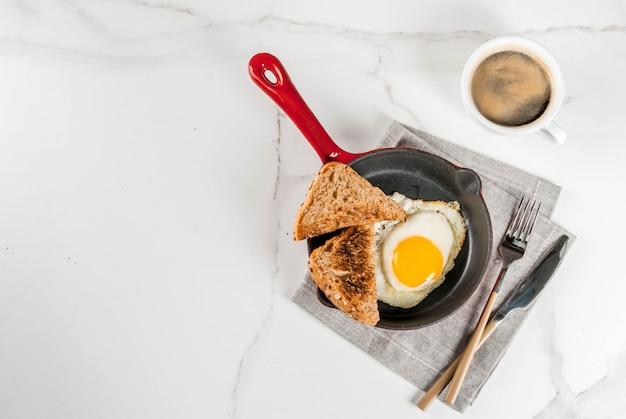 トーストしたパン、鉄鍋で目玉焼き、白い大理石のシーンでコーヒーと朝食
