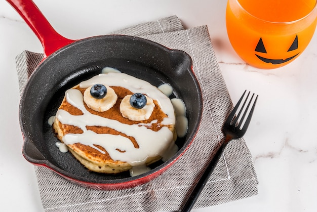 ハロウィーンのおかしい食べ物。ミイラのように飾られた子供の朝食パンケーキ、ホワイトチョコレートソース、バナナ、ベリー、カボチャのスムージージュース、白いテーブル