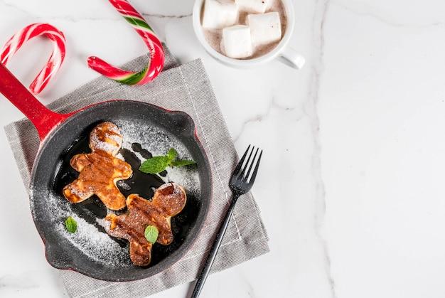 クリスマスの面白い食べ物。ジンジャーブレッドの男性のように飾られた子供の朝食パンケーキ、マシュマロ入りのホットチョコレート、白いテーブル