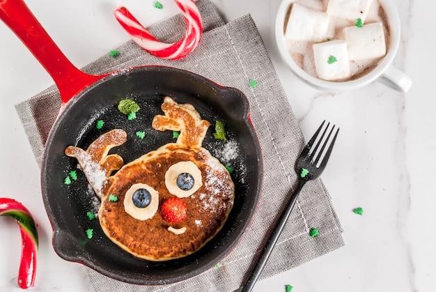 クリスマスの面白い食べ物。トナカイのように飾られた子供の朝食パンケーキ、マシュマロ入りのホットチョコレート、白いテーブル