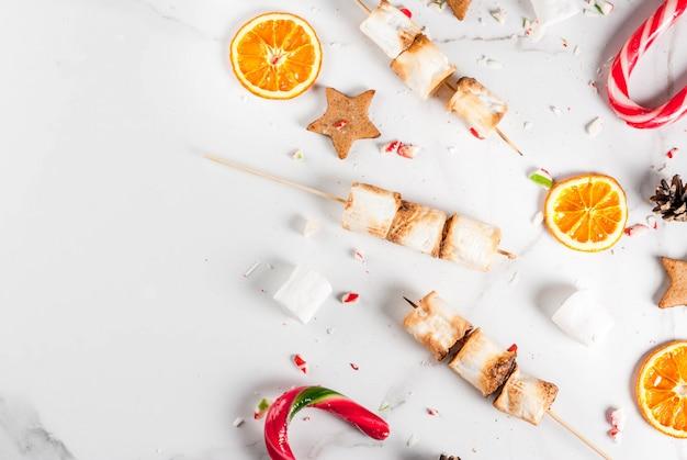 Традиционные рождественские сладости - леденец, зефир, сушеный апельсин, пряничные звезды, запеченные на огне шашлык из зефира на белой мраморной сцене вид сверху