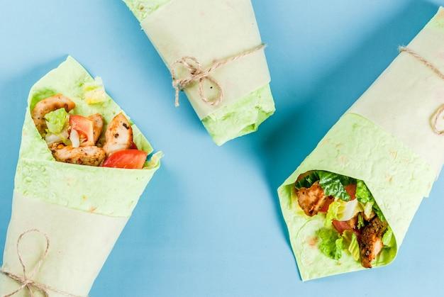 メキシコ料理。健康的な食事。ラップサンドイッチ:ほうれん草入りグリーンラヴァッシュトルティーヤ、フライドチキン、フレッシュグリーンサラダ、トマト、ヨーグルトソース。青いシーン。コピースペーストップビュー