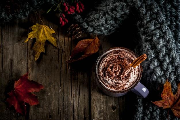 Осенние напитки, горячий шоколад или какао со взбитыми сливками и специями (корица, анис), на старом деревенском деревянном столе, с теплым уютным одеялом, сенной ягодой и листьями.