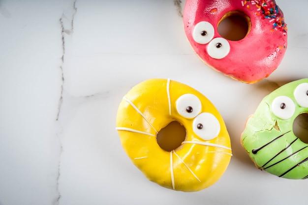 子供向けのアイデアは、ハロウィーンで扱います。モンスターの形のカラフルなドーナツ