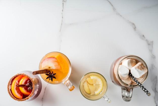 さまざまな秋の伝統的な飲み物のセレクション:マシュマロ入りホットチョコレート、レモンとジンジャー入りの紅茶、白パンプキンのスパイシーなサングリア、ホットワイン。白い大理石のテーブル、トップビュー