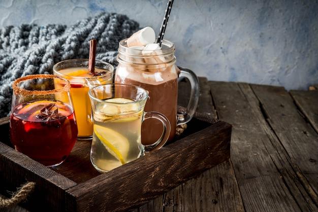 さまざまな秋の伝統的な飲み物の選択:マシュマロ入りホットチョコレート、レモンとジンジャー入りのお茶