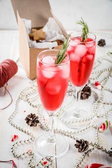 お正月、クリスマスの飲み物。クランベリー、リキュール、ローズマリー、氷と赤いアルコールカクテル。