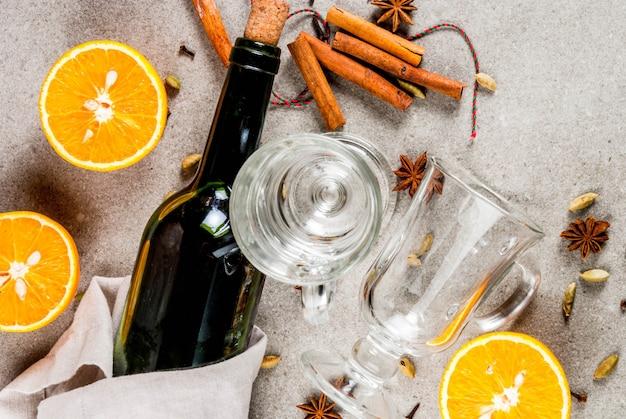 クリスマスホットドリンクレシピ、グリューワインの材料のセット:ワインボトル、ガラスカップ、スパイス、オレンジ。灰色の石、トップビュー