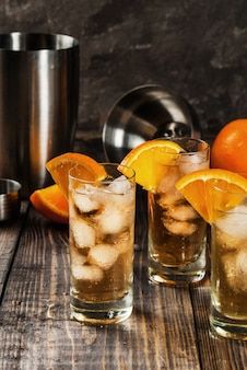 アルコールウォッカウイスキーオレンジハイボールカクテル、オレンジの飾り、木製のテーブルの上