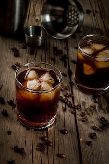 アルコール。飲み物、素朴な木製のテーブルにウォッカとコーヒー酒と大酒飲みブラックロシアンカクテル。