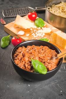 Ингредиенты итальянской кухни. продукты для приготовления пасты болоньезе, процесс приготовления. сваренные спагетти в сковороде, соус болоньезе, базилик, чеснок, помидор, пармезан