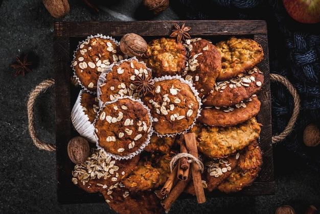 秋冬のペストリー。ビーガンフード健康的な自家製ベーキングクッキー、ナッツ入りマフィン、リンゴ、オート麦フレーク。居心地の良い家庭的な雰囲気、暖かい毛布、食材。暗い石のテーブル。上面図
