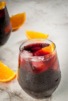 伝統的なスペインの夏の爽やかなドリンクカクテルティントデベラノ。ワインアイスと新鮮なオレンジの破片