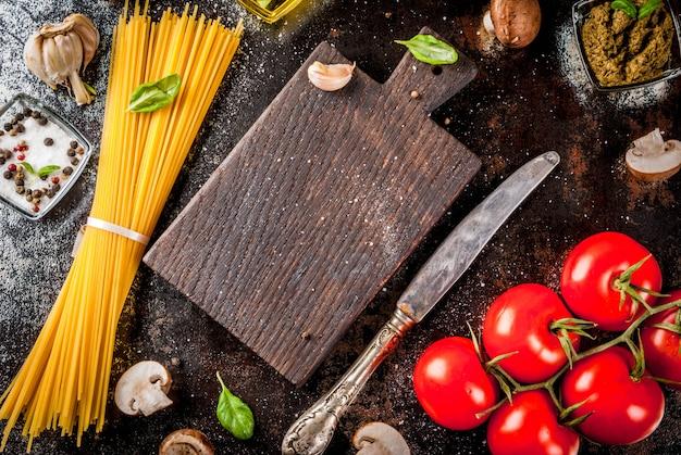 Еда фоновые ингредиенты для приготовления обеда. макароны спагетти овощи соусы и специи темно-ржавый фон
