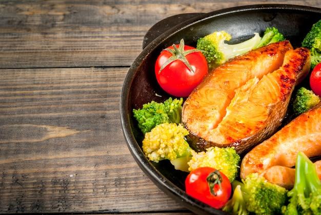 Здоровое питание. запеченная на гриле форель (лосось) с овощным гарниром - помидорами брокколи. в порционной сковороде на деревянном столе. закрыть просмотр