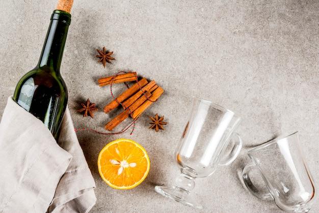 クリスマスホットドリンクのレシピグリューワインの材料のセット:ワインボトルスパイスオレンジ