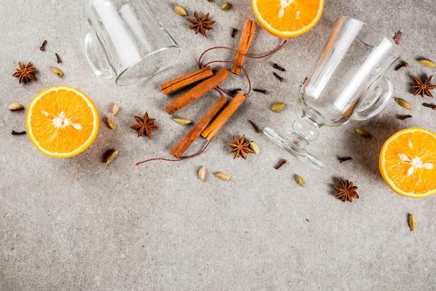 Рождественские рецепты горячих напитков набор ингредиентов для глинтвейна: две стеклянные чашки специй апельсин.