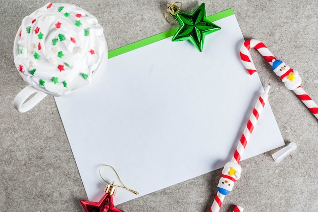 グリーティングシート、クリスマスデコレーション、ホットチョコレートのカップ、キャンデー杖の形のペンが付いた灰色のテーブル。書いている女の子、画像、上面図、雪の効果で女性の手