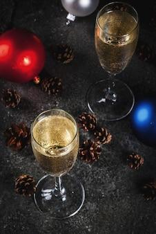 Сухое шампанское в бокалах, разноцветные елочные шары, сосновые шишки, натюрморт на темном камне, селективный фокус
