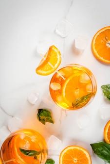 夏の爽やかなドリンク、レモネード、オレンジとバジルのカクテル。白い大理石のテーブル、トップビュー