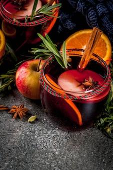 伝統的な冬と秋の飲み物。クリスマスと感謝祭のカクテル。オレンジ、リンゴ、ローズマリー、シナモン、スパイスが入った暗い石のホットワイン、