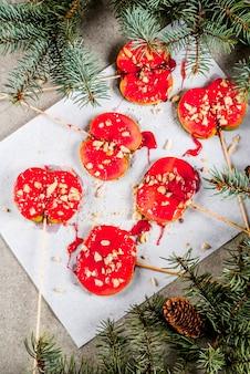 Идеи зимы, рождественские угощения. сладости для детей. шоколадное яблоко ломтики красной карамели и орехов. серый камень фон, с еловыми ветками, вид сверху копией пространства