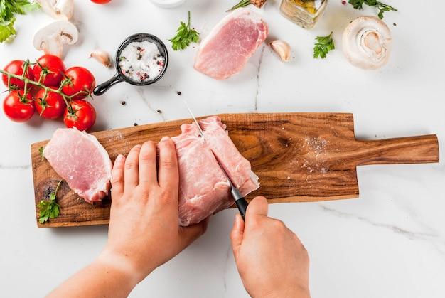 生の肉と夕食の食材。豚ヒレ肉、テンダーロイン、まな板の上、塩、コショウ、パセリ、ローズマリー、オイル、ニンニク、トマト、キノコを切り取った。黒い石のテーブル、コピースペース