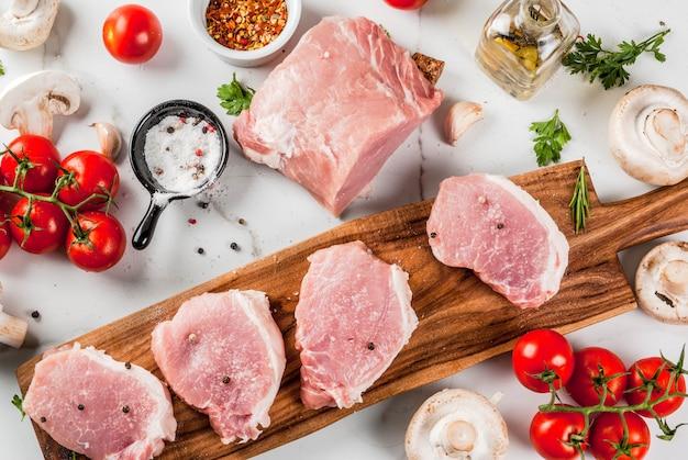 生の肉と夕食の食材。豚ヒレ肉、テンダーロインステーキ、まな板の上、塩、コショウ、パセリ、ローズマリー、オイル、ニンニク、トマト、マッシュルーム添え。黒い石のテーブル、コピースペース平面図