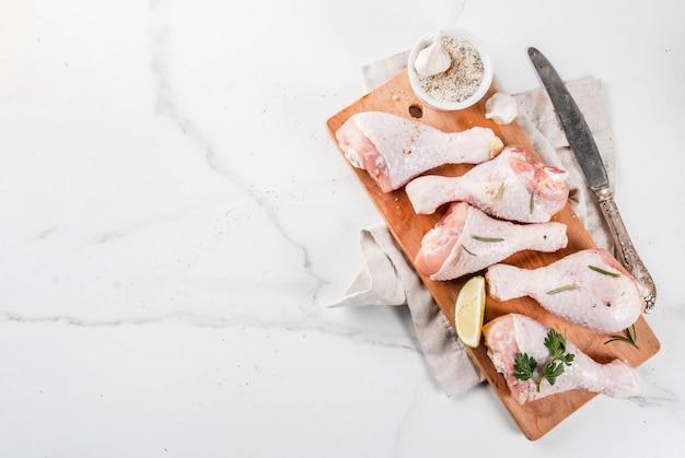 Сырое мясо, куриные ножки, с оливковым маслом, травами и специями, на белом фоне мрамора, копией пространства вид сверху