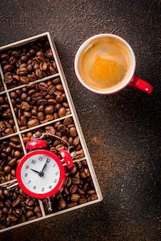 Концепция веселого, хорошего начала дня, утренний кофе. темный ржавый фон с кофе в зернах, будильник и чашка кофе. вид сверху копией пространства