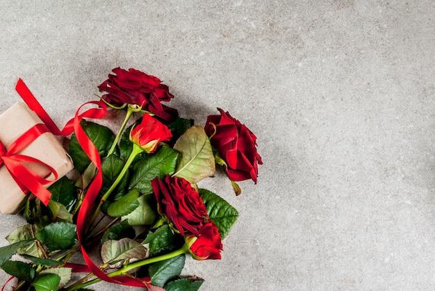 休日、バレンタインデー。赤いバラの花束、赤いリボンとネクタイ、ラップされたギフトボックスと赤いろうそく。灰色の石のテーブル、トップビュー