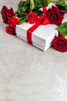 休日、バレンタインデー。赤いバラの花束、赤いリボンとネクタイ、ラップされたギフトボックス。灰色の石のテーブルの上に、