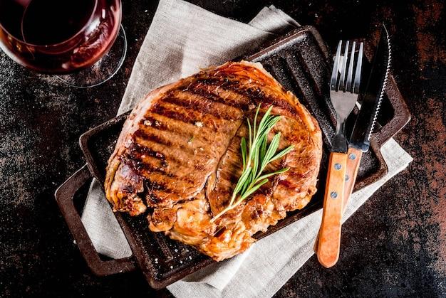 グリル鍋ボードにスパイスと牛肉のグリルステーキ、赤ワイングラス。上面図
