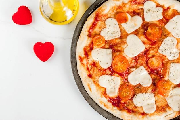 Валентина праздничная еда, пицца маргарита с сыром в форме сердца, белый мрамор, вид сверху