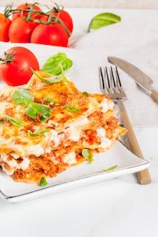 Итальянский рецепт еды. ужин с классической лазаньей болоньезе с соусом бешамель, сыром пармезан, базиликом и помидорами, на белом, холодном месте