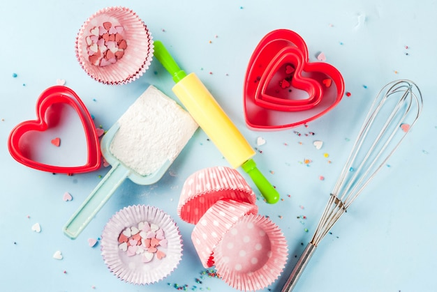 バレンタインデーのための甘いベーキング、麺棒で焼く料理、泡立て器のための泡立て器、クッキーカッター、砂糖の振りかけ、小麦粉。明るい青の背景、トップビュー