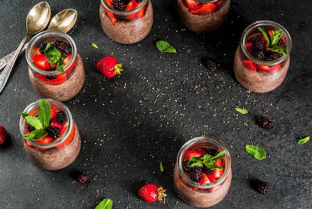 健康的なビーガン朝食。デザート。代替食品。チアシード、新鮮なイチゴ、ブラックベリー、ミントのプリン。 。上面図