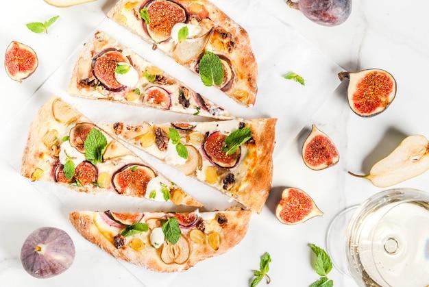 秋のベーキングレシピ。イチジク、ナシ、ブドウ、クリームチーズ、クルミ、ミントの甘いパイピザまたはフルーツフォカッチャ。白ワイングラス、白大理石、上面図