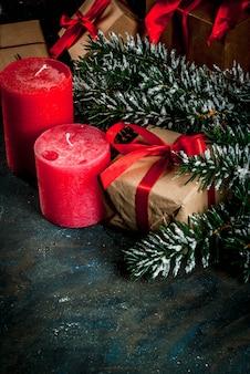 Рождественский фон для поздравительной открытки. елочные ветки с эффектом снега с праздничной красной лентой, сосновые шишки, подарочные коробки и свечи, на синем фоне
