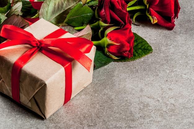 休日の背景、バレンタインの日。赤いバラの花束、赤いリボンとネクタイ、ラップされたギフトボックスと赤いキャンドル