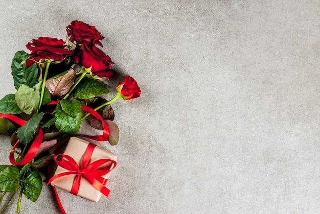 休日の背景、バレンタインの日。赤いバラの花束、赤いリボンと結び、ラップされたギフトボックスと赤いキャンドルトップビュー