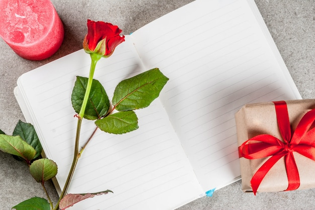 休日の背景、バレンタインの日。赤いバラの花束、空のメモ帳、ラップされたギフトボックス、赤いろうそくの上面と赤いリボンとネクタイ