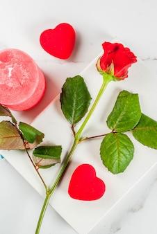 休日の背景、バレンタインの日。赤いバラの花束、空白のメモ帳、赤いギフトボックス、赤いろうそく、赤いリボンとネクタイ。白い大理石のテーブルトップビュー